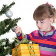 Pretty little girl is opening a christmas gift - Stock Photo