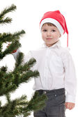 Handsome toddler in christmas hat decorating new year tree — Stock Photo