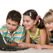 Kids with laptop on the carpet - Stockfoto