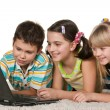 Kids with laptop on the carpet — Stock Photo