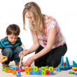 Stock Photo: Mother and son playing on carpet