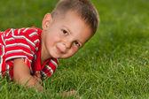 Niño en rojo sobre la verde hierba — Foto de Stock