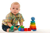 Serious baby boy with toys — Stock Photo