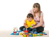 Mother and son on the carpet with toys — Stock Photo
