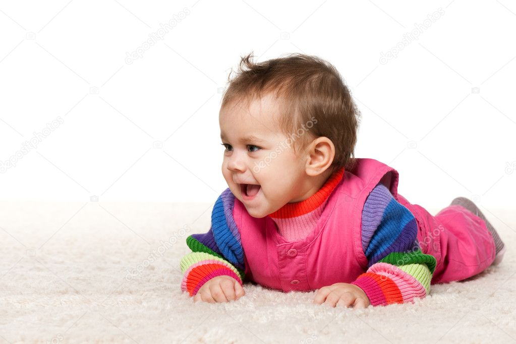 A baby girl is lying on the carpet; isolated on the white background — Stock Photo #9501949