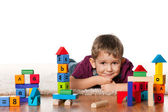Little boy on the floor near toys — Stock Photo