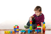 Handsome little boy on the floor with toys — Stock Photo
