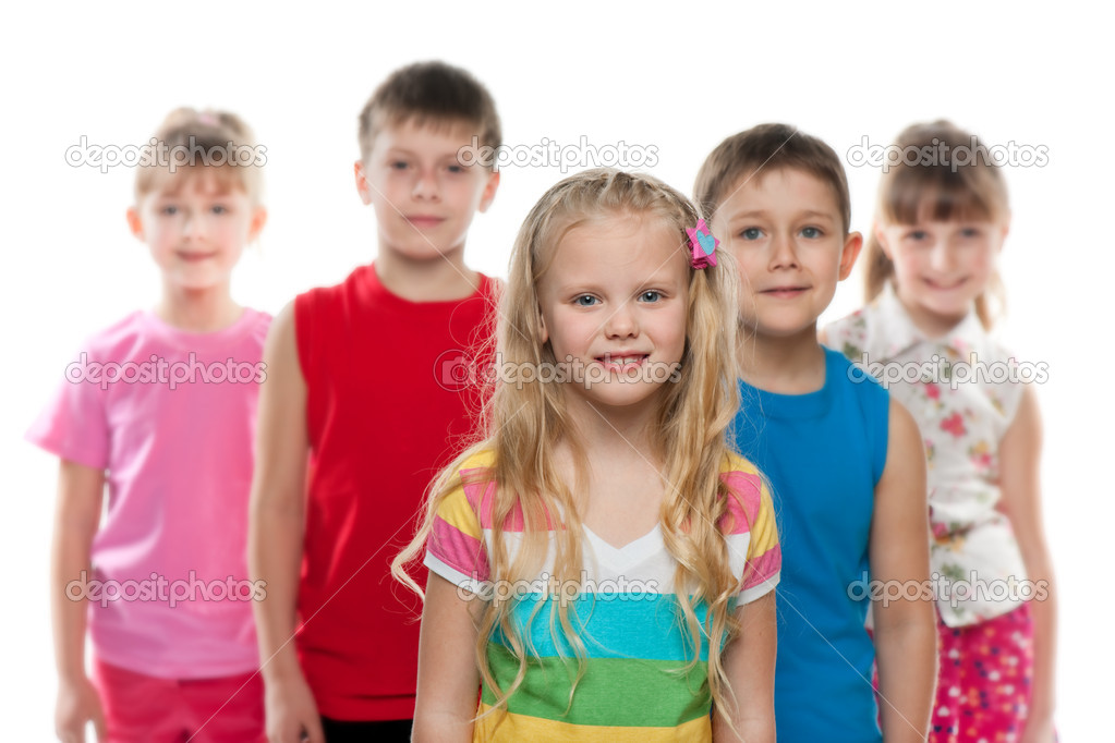 A little girl stands in front of a group of children, focus is on the girl; isolated on the white background  Stock Photo #9839239
