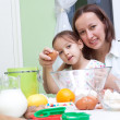 Stock Photo: Mother and her daughter, bakeing in kitchen