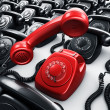 Red rotary phone surrounded by black phones — Stock Photo