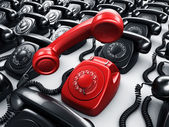 Red rotary phone surrounded by black phones — ストック写真