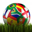 Soccerball with flags in grass — Stock Photo