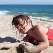 Little Girl Relaxing on the Beach Covered in Sand — Stockfoto