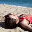 Close up of a Little Girl Relaxing on the Beach Covered in Sand — Stock Photo #9132627