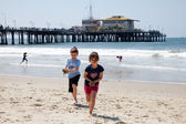 Ragazza e ragazzo che giocano sulla spiaggia — Foto Stock