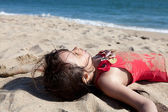 Close up of a Little Girl Relaxing on the Beach Covered in Sand — Stock Photo