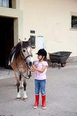 Little girl ready for a horseback riding lesson — Stock Photo