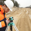 Road construction, land surveyor looking at equipment - Stock Photo