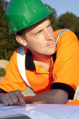 Manual worker looking on blueprint, road construction — Stock Photo