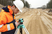 Road construction, land surveyor looking at equipment — Stock Photo