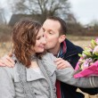Stock Photo: Lovers Kissing With Bouquet