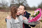 Amantes de besos con bouquet — Foto de Stock