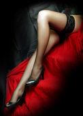 Belles jambes minces en nylons noirs sur fond rouge. — Photo