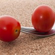 Stock Photo: Two small red tomatoes on fork on cork background