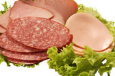 Pieces of salami and ham on lettuce leaf isolated on white back — Stock Photo