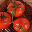 Three fresh red tomato on woven plate - Photo