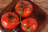 Three fresh red tomato on woven plate — Stockfoto