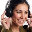 Beautiful Customer Representative with headset smiling during a telephone c — Stock fotografie
