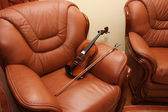 Violin on Leather Chair — Stock Photo