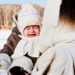 Mum with crying baby outside in cold - Stock Photo