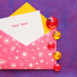 Pink envelope with white circles and a note — Stock Photo