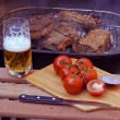 Steaks on grill and beer - Stock Photo