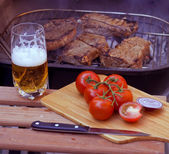 Steaks on grill and beer — Stock Photo