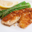 Fried breaded fish with asparagus and lemon - Stock Photo