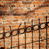 Shadow of a fence on a brick wall — Stock Photo