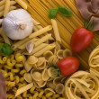 Different kind of raw pasta with tomatoes garlic and basil — Photo