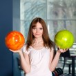 Young pretty girl with two bowling balls. - Stock Photo