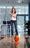 Rolling bowling ball and happy girl in the background. — Stock Photo
