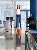Rolling bowling ball and happy jumping girl in the background. — Stock Photo
