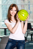 Young smiling girl with green bowling ball — Stock Photo