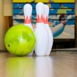Green bowling ball and pins — Stock Photo
