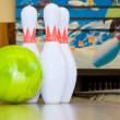 Green bowling ball and pins — Stock Photo