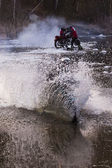 Motorcycle forcing the river — Stock Photo