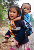 A little girl with her brother on her back — Stock Photo