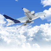 Airplane flying over the clouds at takeoff bottom view — Stock Photo