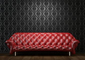 Red leather couch on black wall — Stock Photo